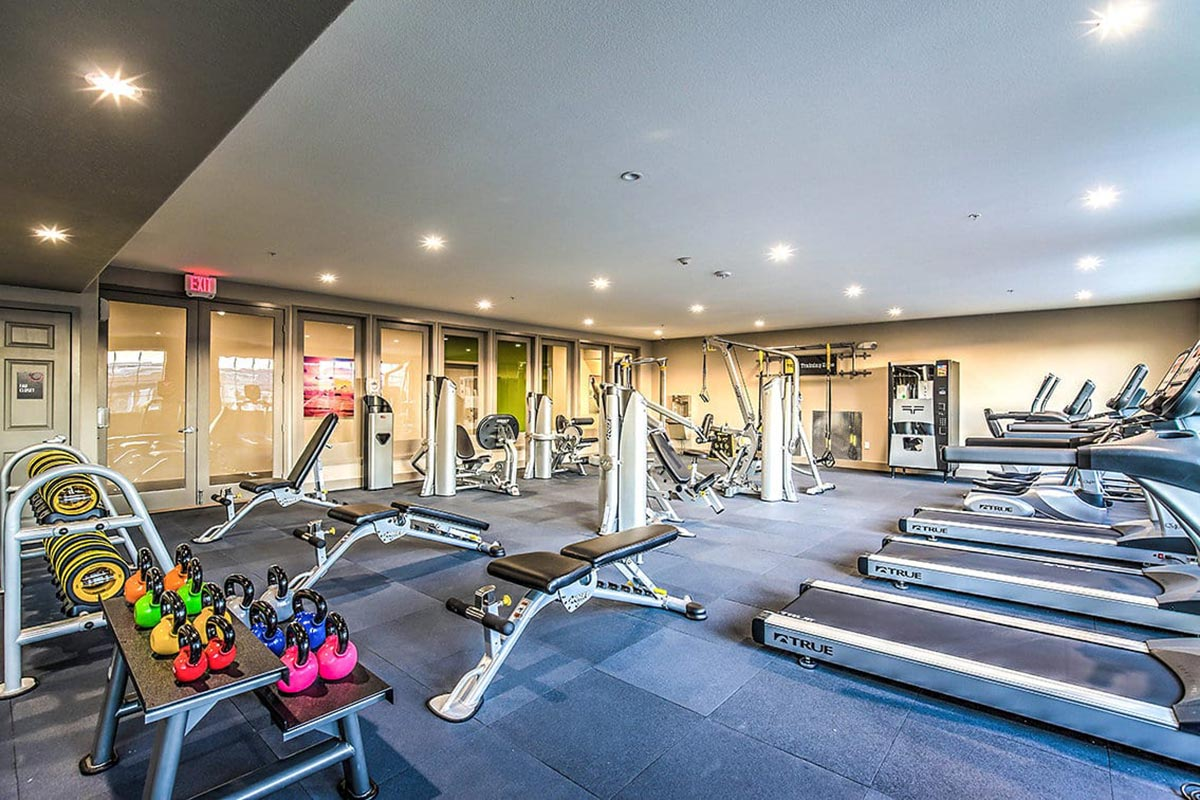 Community fitness center with cardio and weight machines, weights racks, and vending machine.