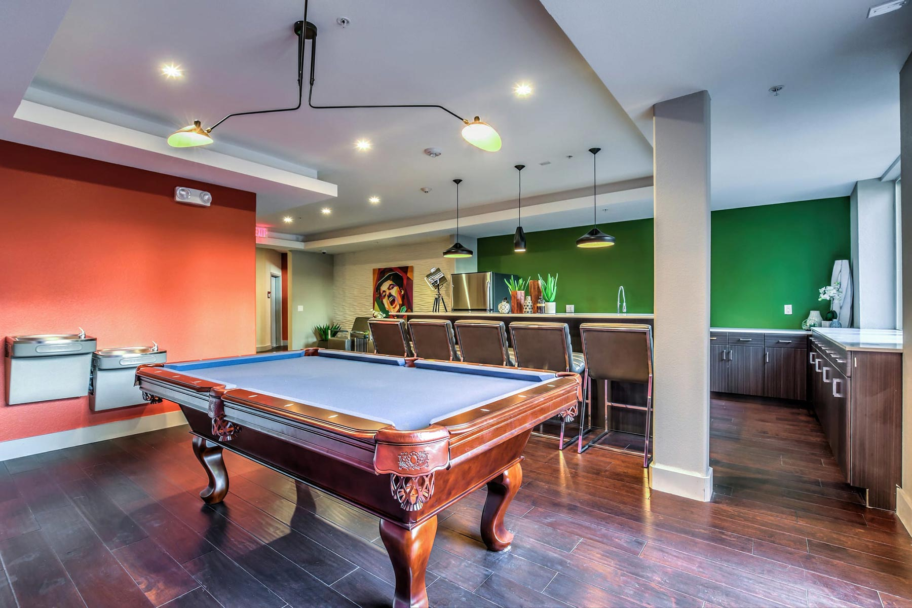 Billiards table in the community entertainment room. There is a kitchen with breakfast bar seating.