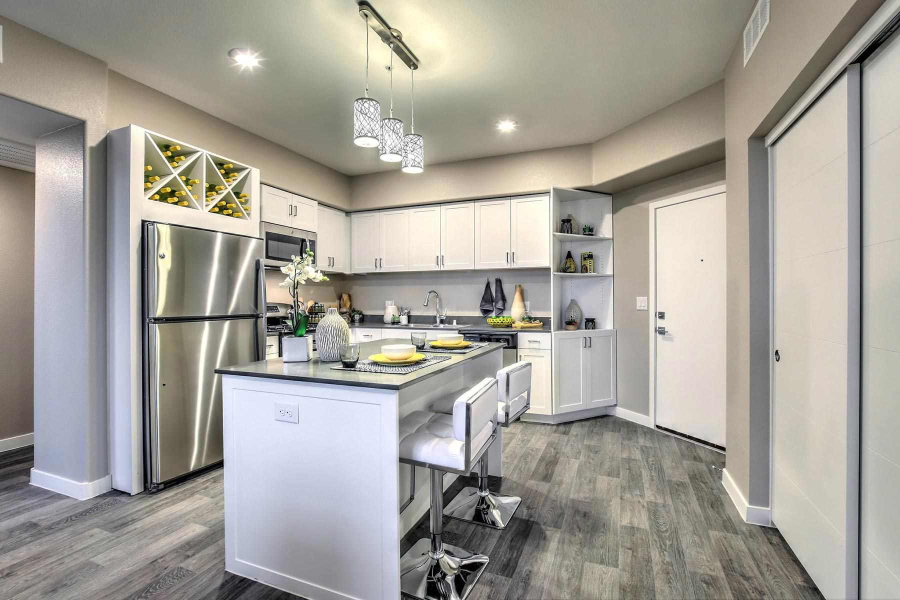Open-concept kitchen featuring island with bar seating, quartz countertops, wood-style flooring, modern cabinetry, and Energy Star GE appliances. There is pendant lighting, wine storage, and a closet on the right. The entrance to the apartment beings in the kitchen.