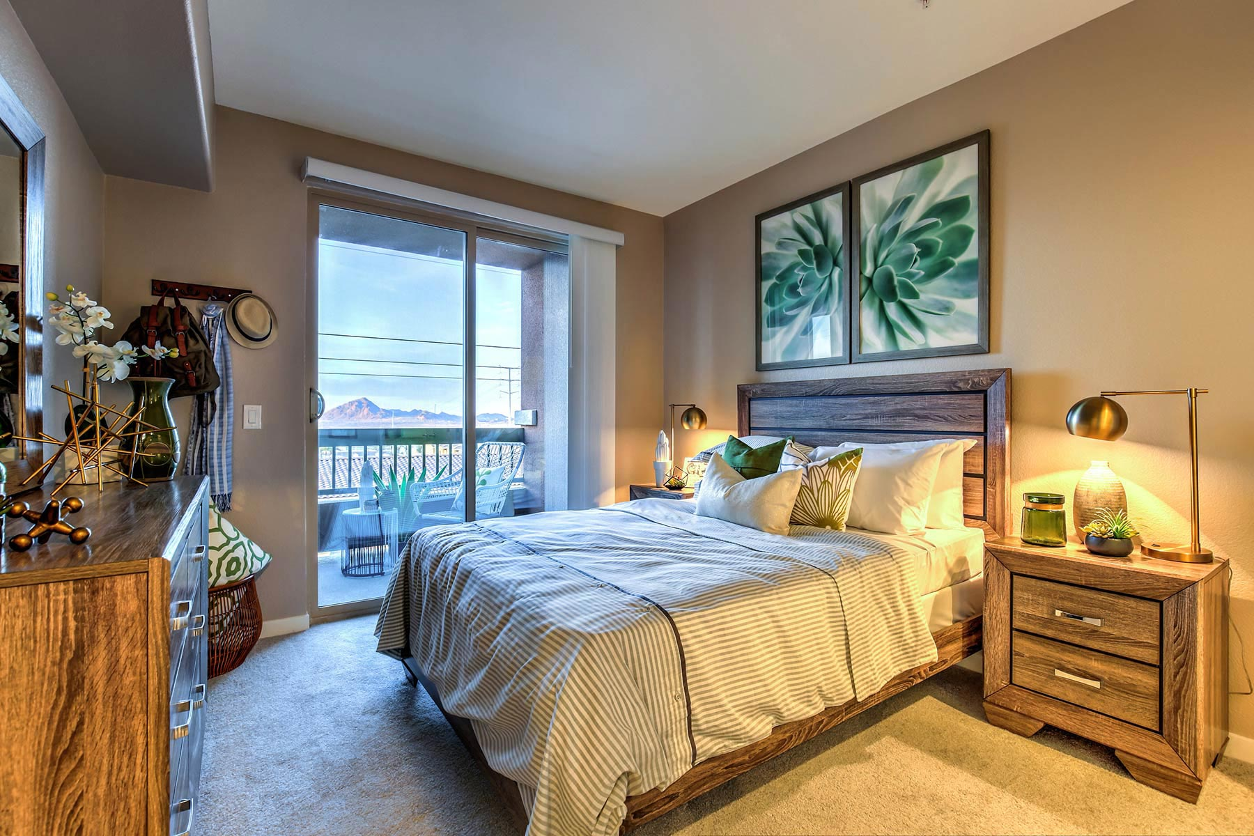 Carpeted bedroom with high ceilings. Sliding glass doors lead to the private patio/balcony with mountain views.