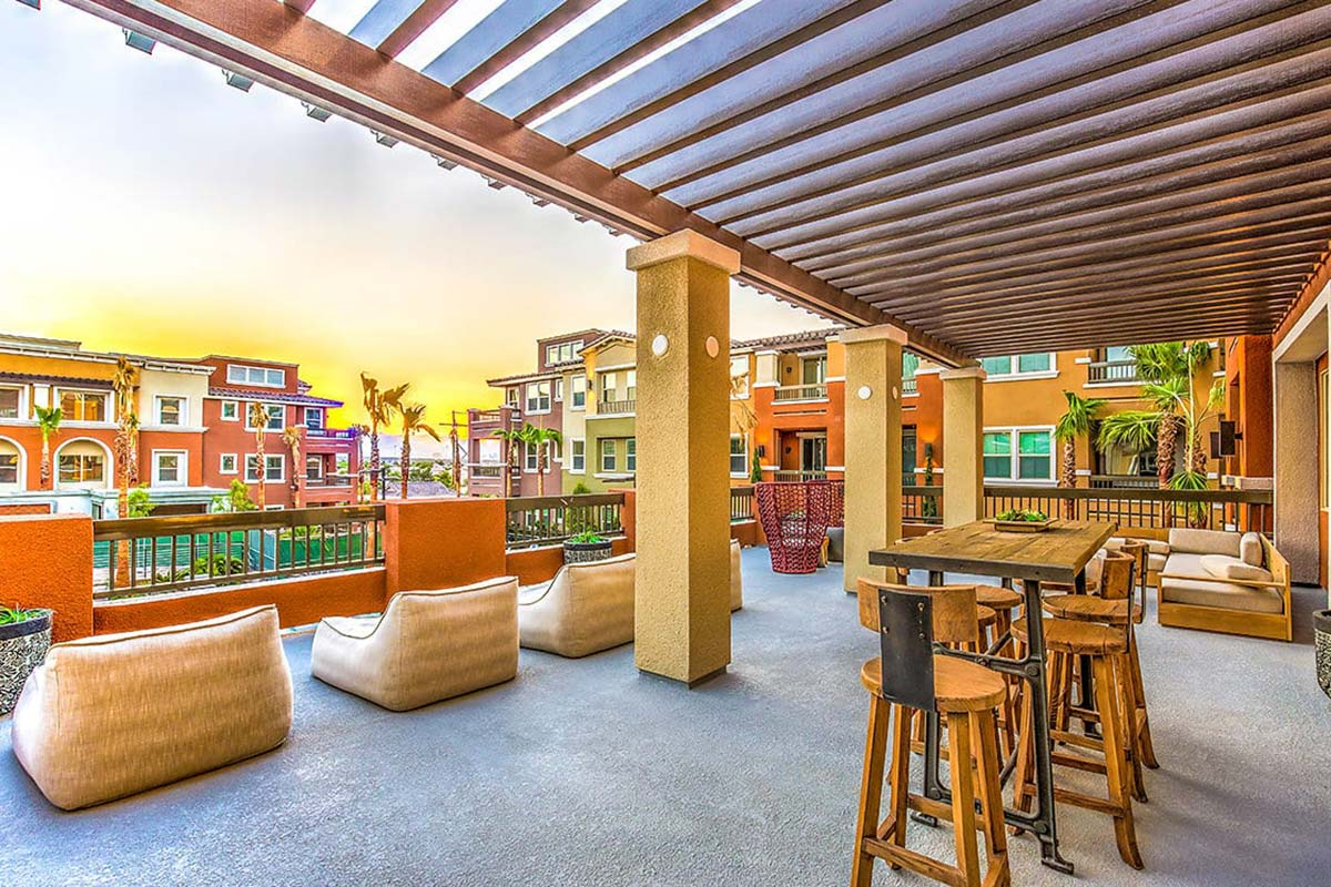 Upstairs outdoor dining terrace with lounge seating and tables overlooking community courtyard.