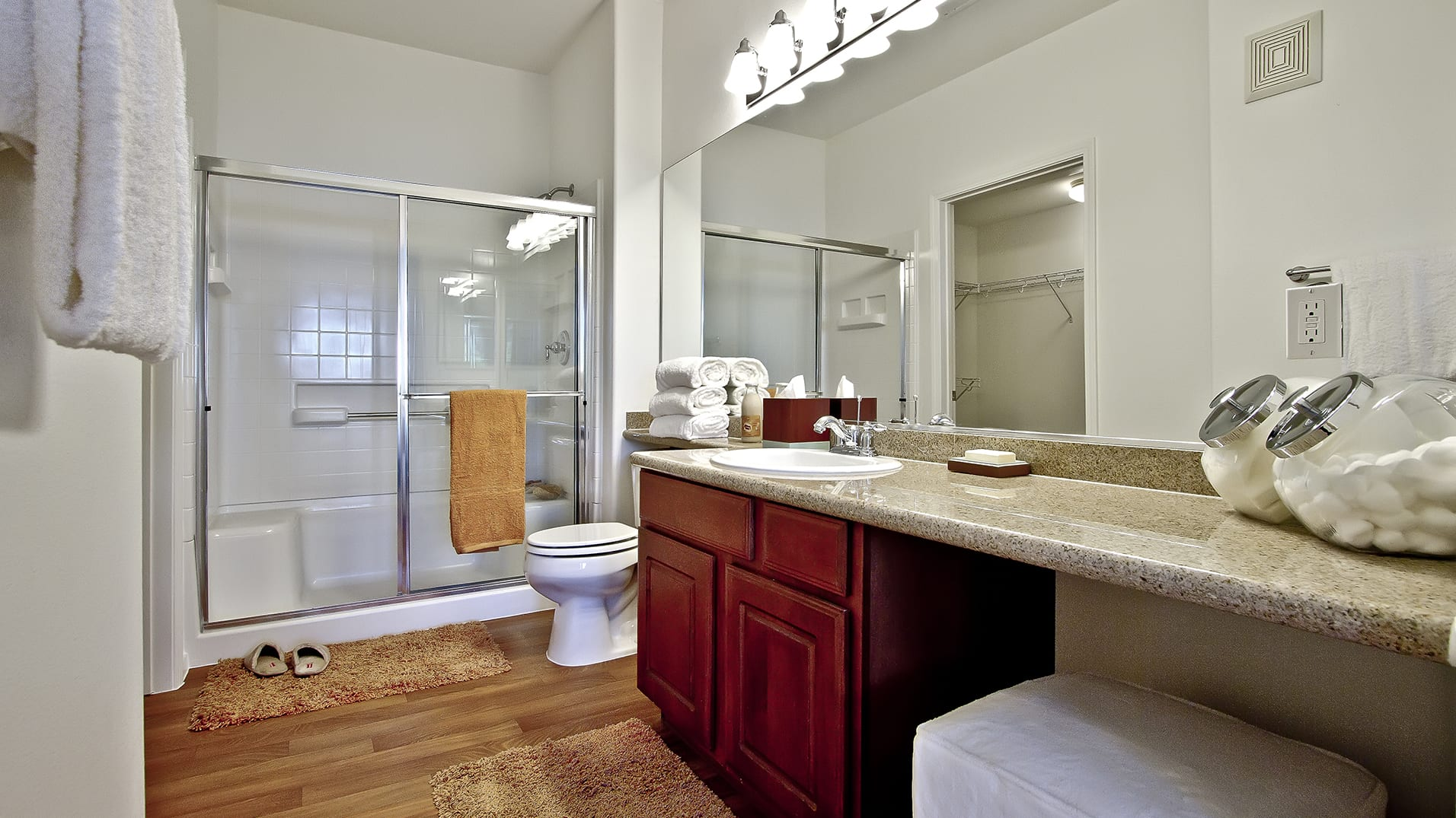 Spacious bathroom with wood-style flooring, walk-in shower with bench, and oversized vanity with granite countertop.