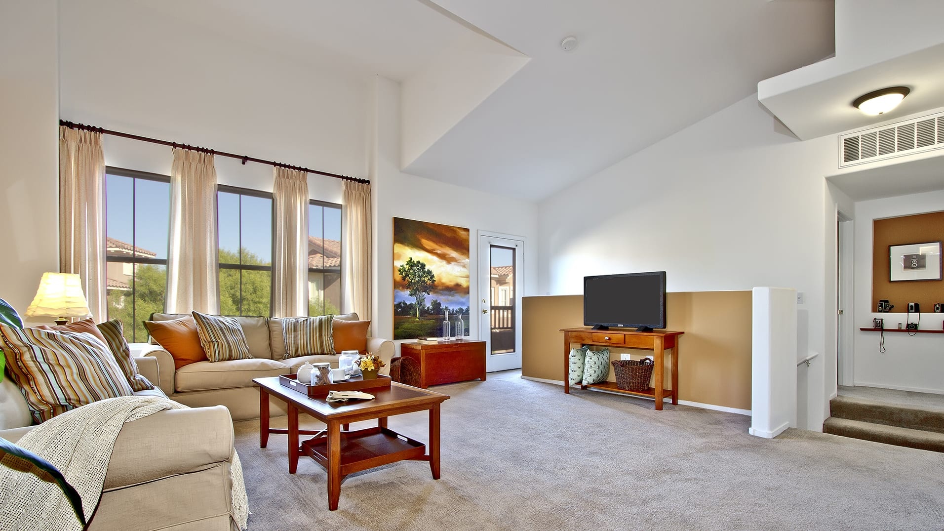 Spacious carpeted living room with high vaulted ceiling, large windows, interior staircase, and door to privative balcony.