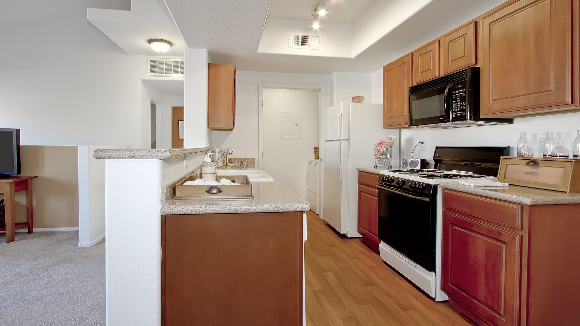 Kitchen with full appliance package, wood-style flooring, and granite countertops. A partial wall looks out into the carpeted living room. Beyond the kitchen is the laundry room with washer and dryer.