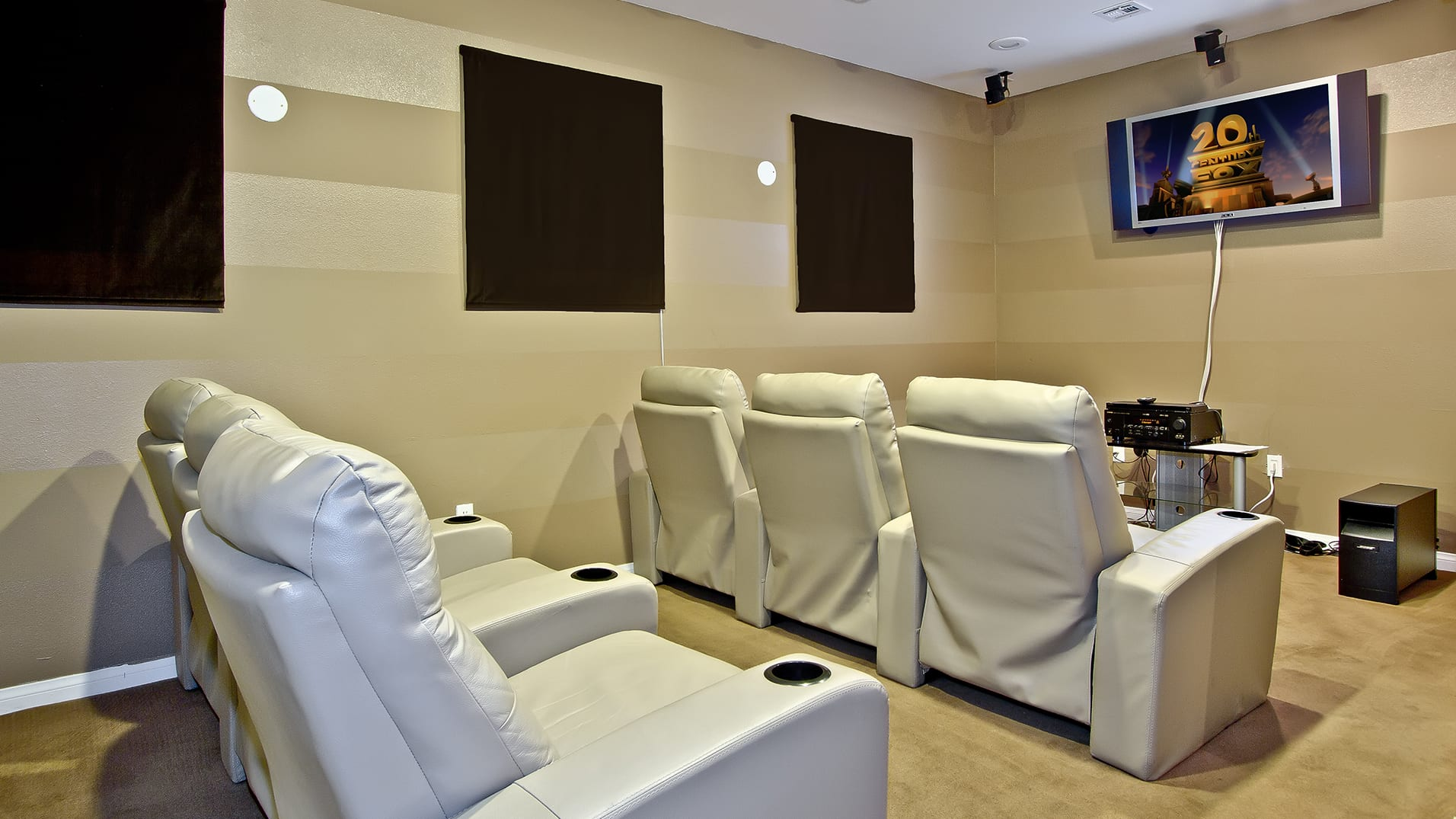 Community movie theater room with comfortable lounging arm chairs and flat-screen TV.
