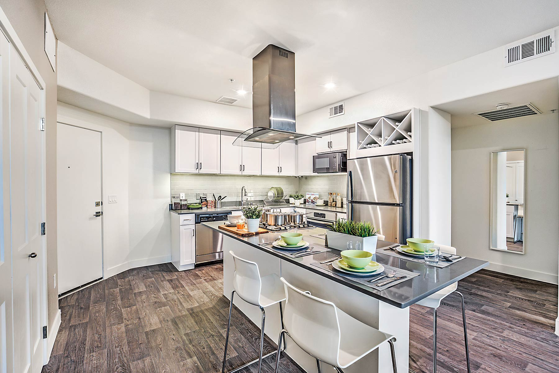 Contemporary kitchen with large island with bar seating, white cabinetry, quartz countertops, Energy Star GE appliances, and wood-style flooring.