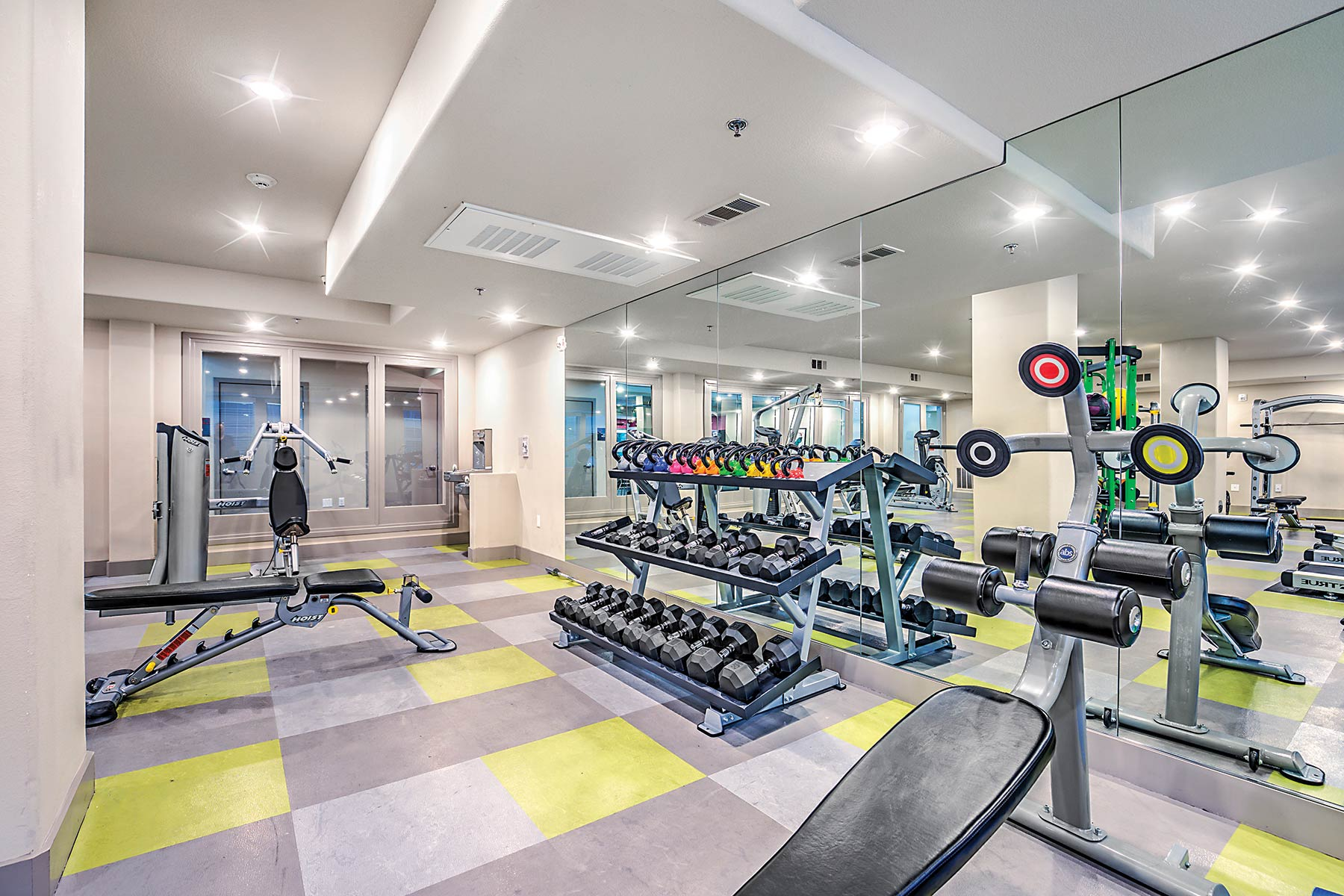 Spacious fitness center with mirrored wall, weights rack, and weight and cardio machines.
