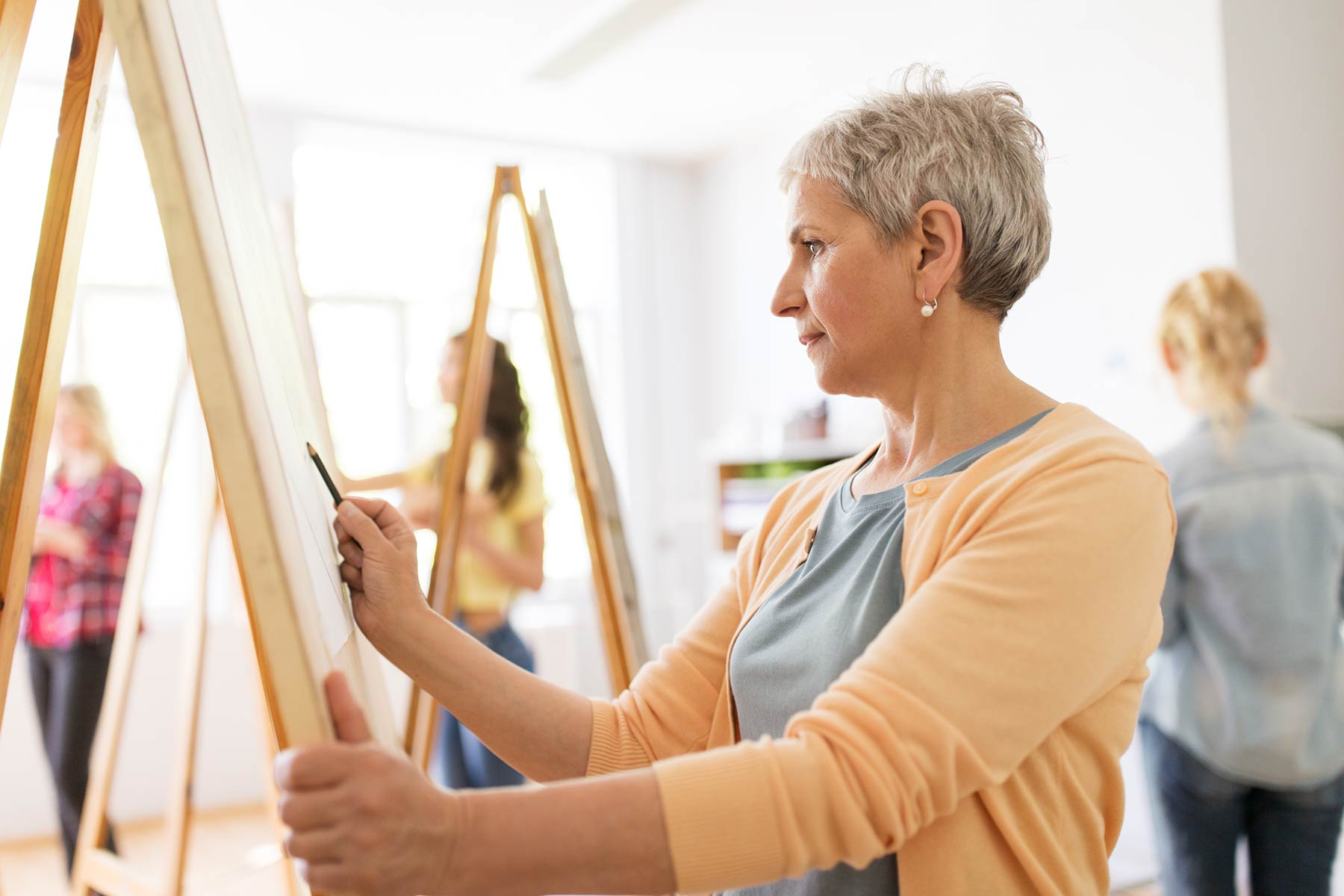 50 to 60 year old woman drawing against an easel in a class with other people.