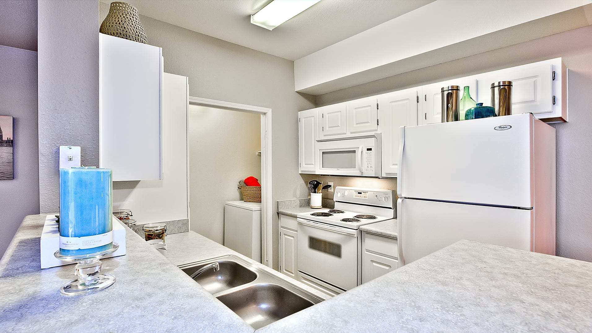 Kitchen with white cabinetry and full appliance package. Through the kitchen is entry to the laundry room.