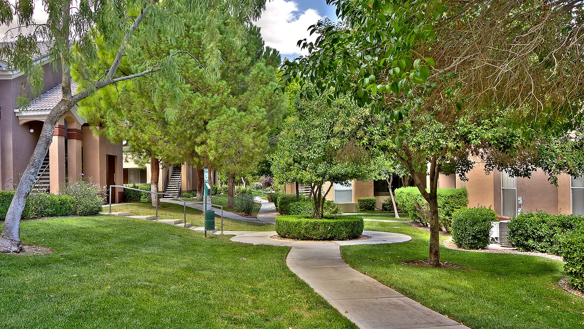 Professional landscaping, dog park area, and paved walkways amidst large trees between apartment buildings.