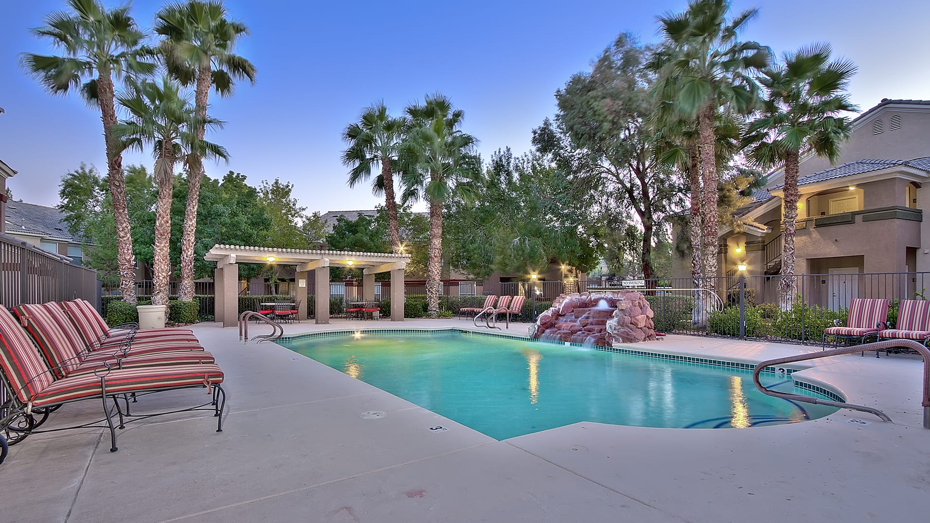 Gated resort-style pool with stone waterfall feature, cushioned lounge seating, covered patio area with tables and chairs, and large palm trees surrounding.