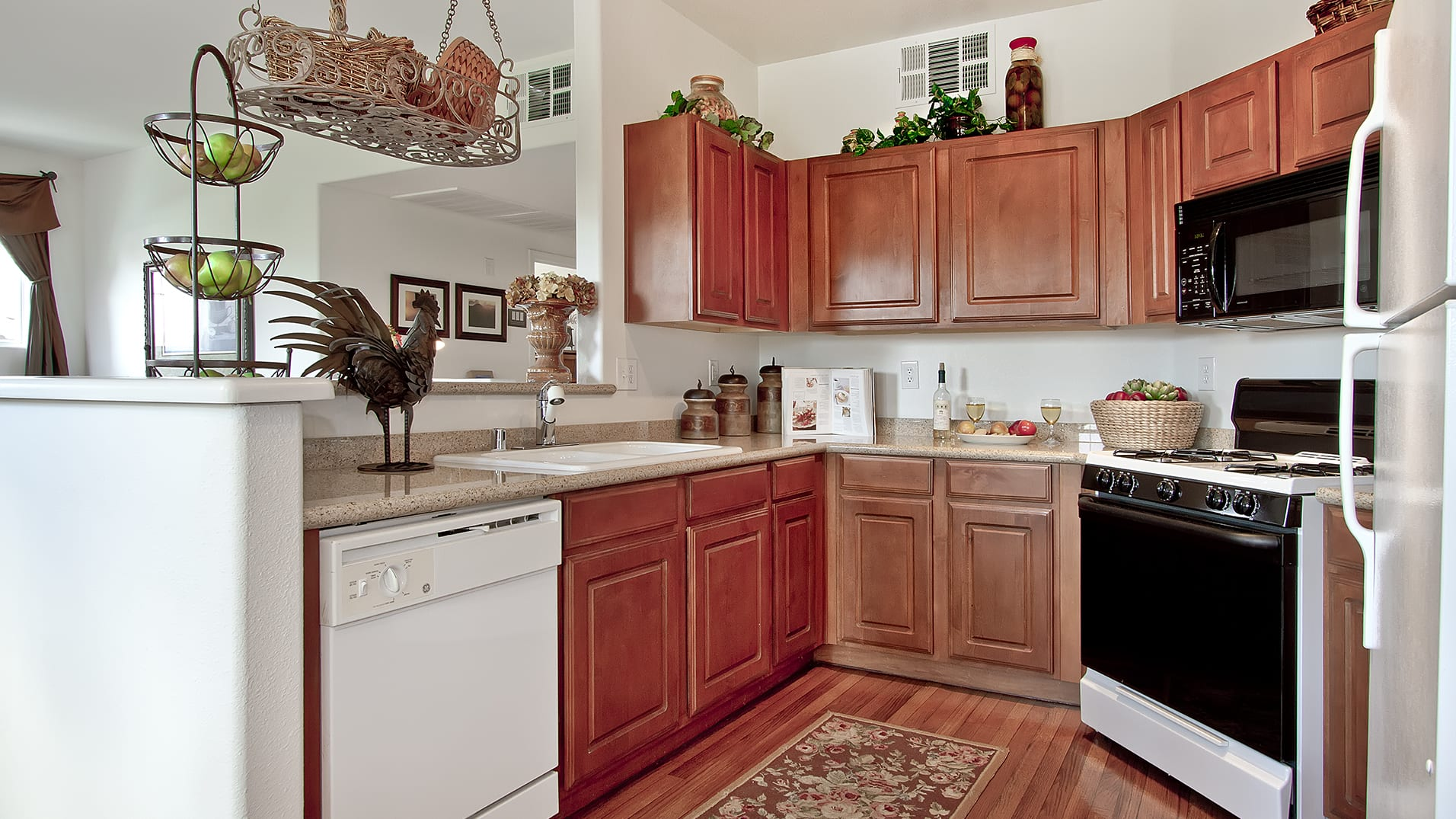 A kitchen with wood cabinets, smooth countertops, and a spacious sink.
