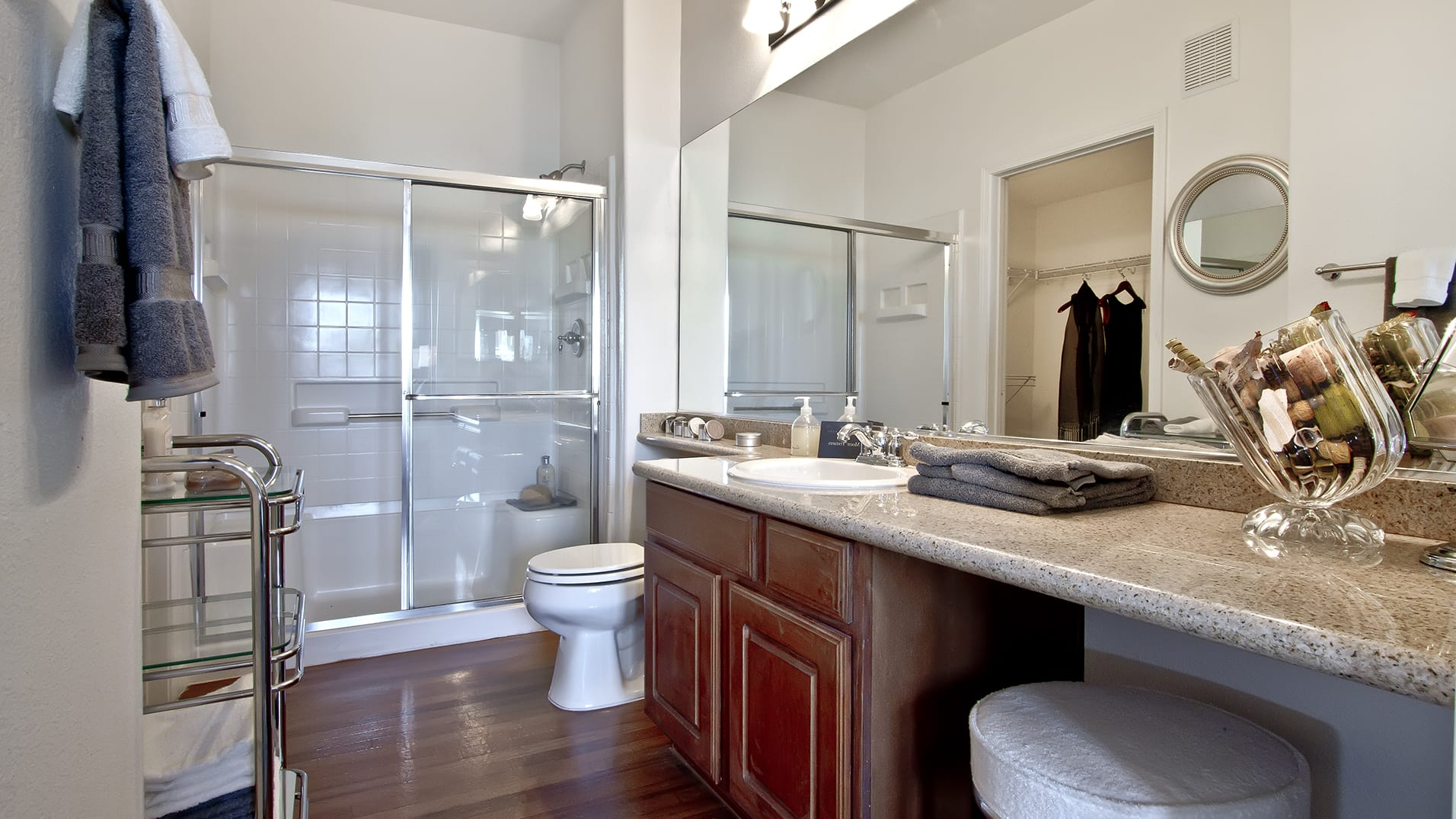 A spacious bathroom with rich wood-like floors, ample storage, and sliding glass shower doors.