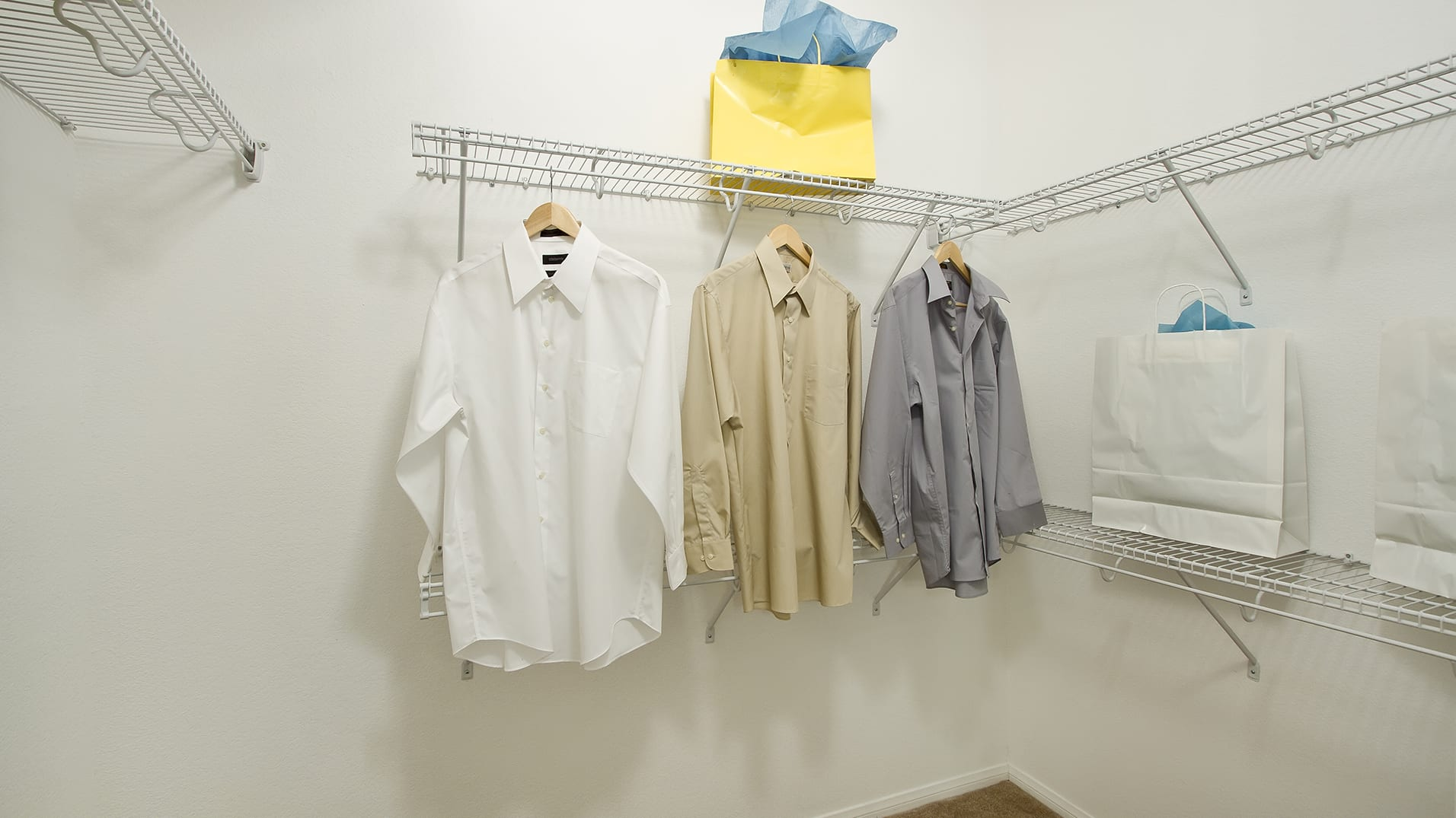 A spacious closets with a selection of shirts and shevles supporting shopping bags.