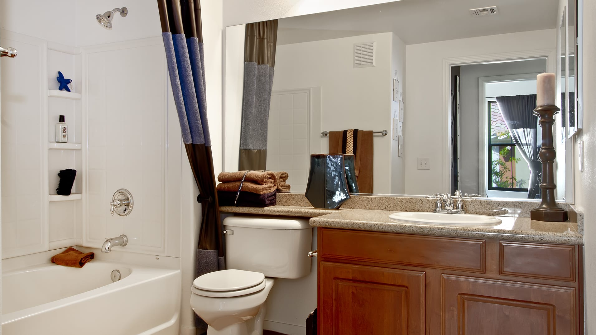 A bathroom with wood cabinets, smooth countertops, and a spacious shower.