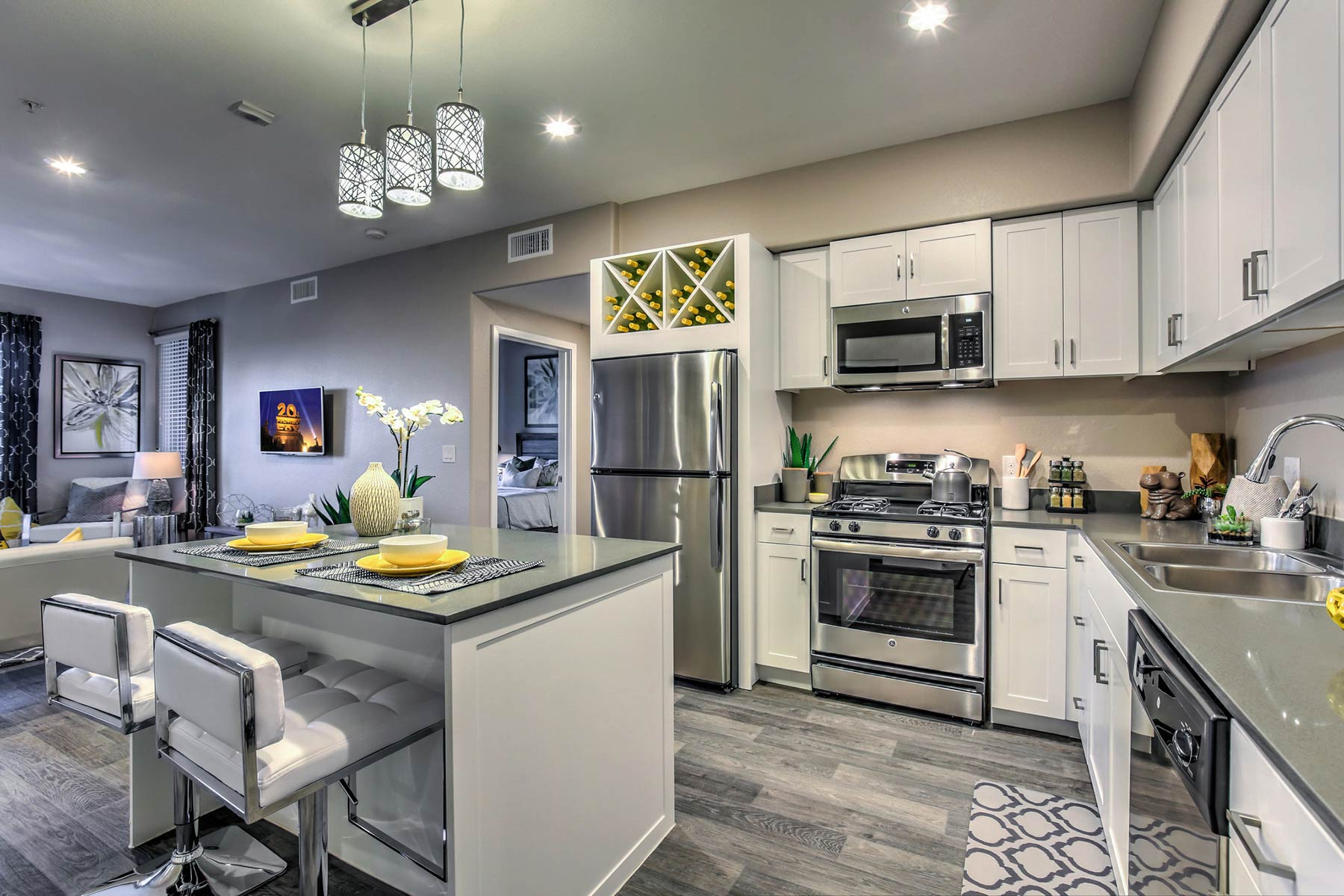 An open-concept kitchen with wood-style flooring, quartz countertops, large island, pendant lighting, white cabinetry, and stainless steel appliances. The kitchen overlooks the living room.