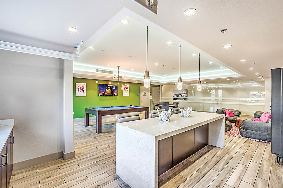 Community entertaining room with lounge seating, pool table flat-screen TV, and modern demonstration kitchen.