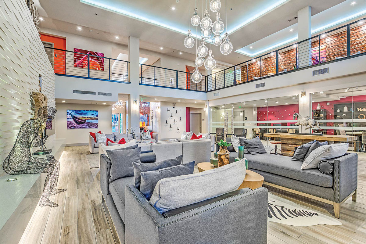 Expansive community clubhouse lounge with mezzanine level. There is plush lounge seating, artistic decorations, and a conference room and business center in the background, enclosed by glass walls.
