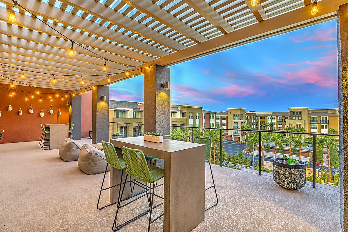 Expansive outdoor dining and lounge terrace with string lights, bean bags, and high-top dining tables. The balcony overlooks the resort-style community pool and apartment buildings in the background.