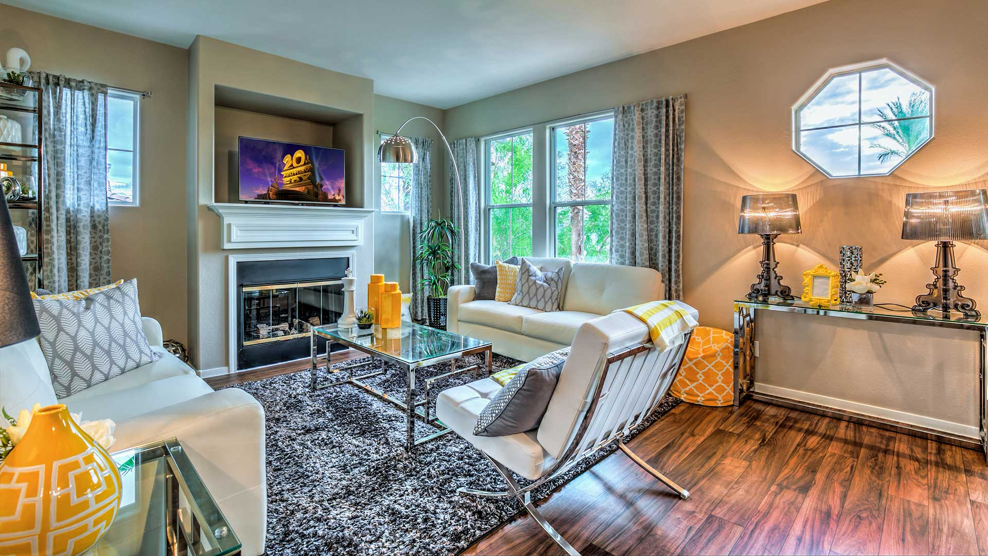 A comfortable living room with a soft rug, plush couches, and a warm fireplace.