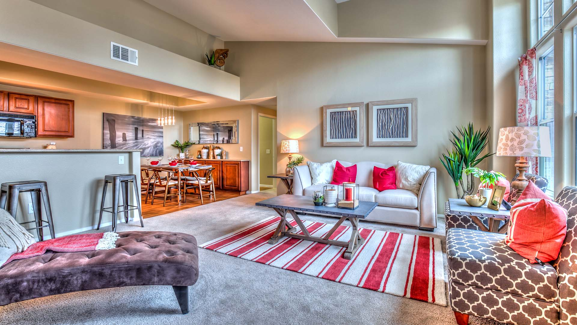 A living room with tall vaulted ceilings, soft carpet, and plush furniture.
