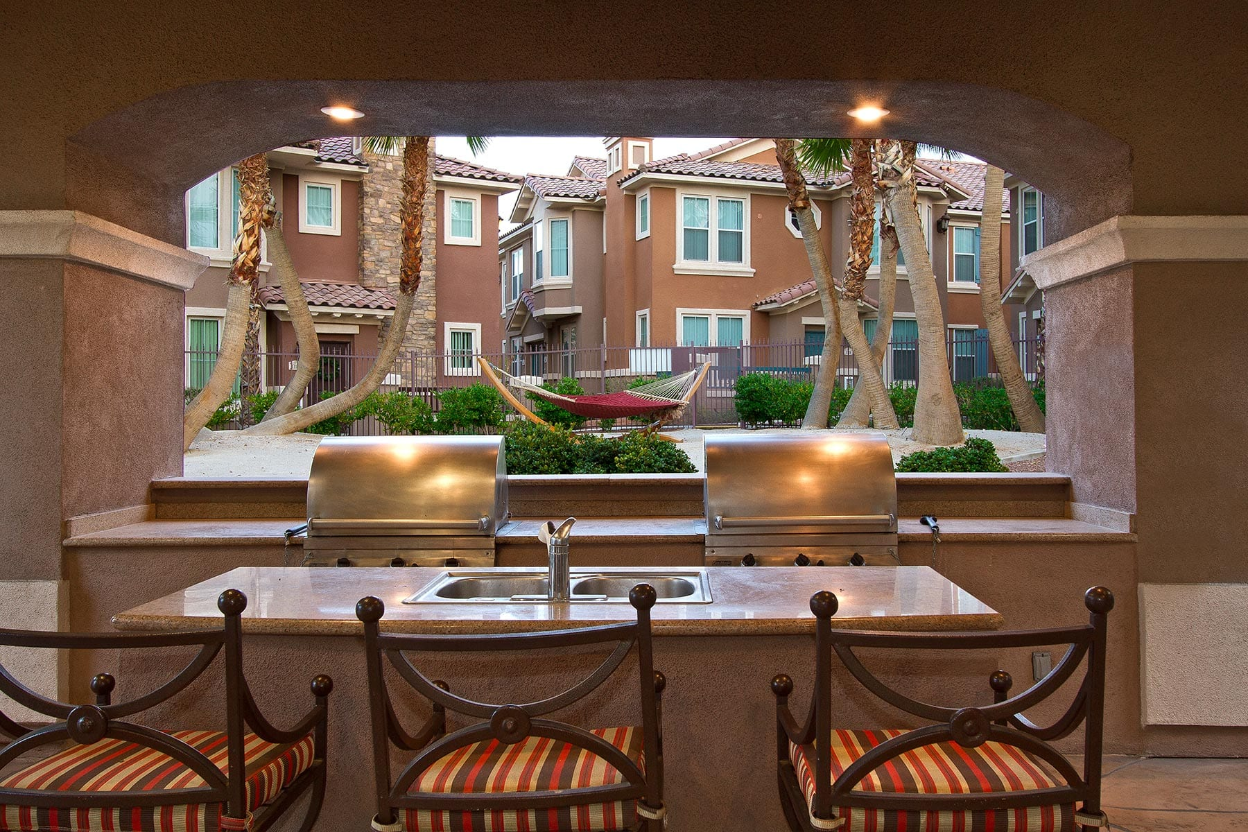 Comfortable high chairs sit in front of a bar top with built-in BBQ grills within a covered outdoor patio.