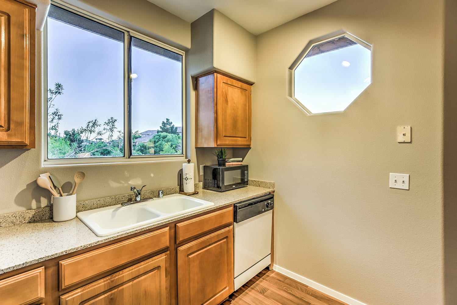 A warm kitchen with wooden cabinets, smooth countertops, and an interesting octagonal window.