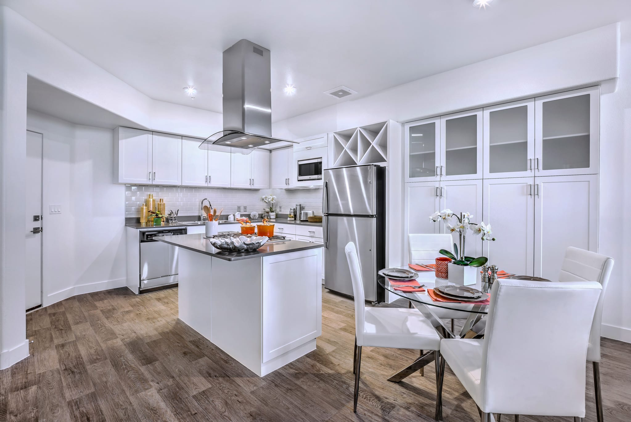 Contemporary kitchen with wood-style flooring, large island, quartz countertops, stainless steel appliances, tile backsplash, and extended white cabinetry. The open-concept layout includes a round dining table with dinner placements.