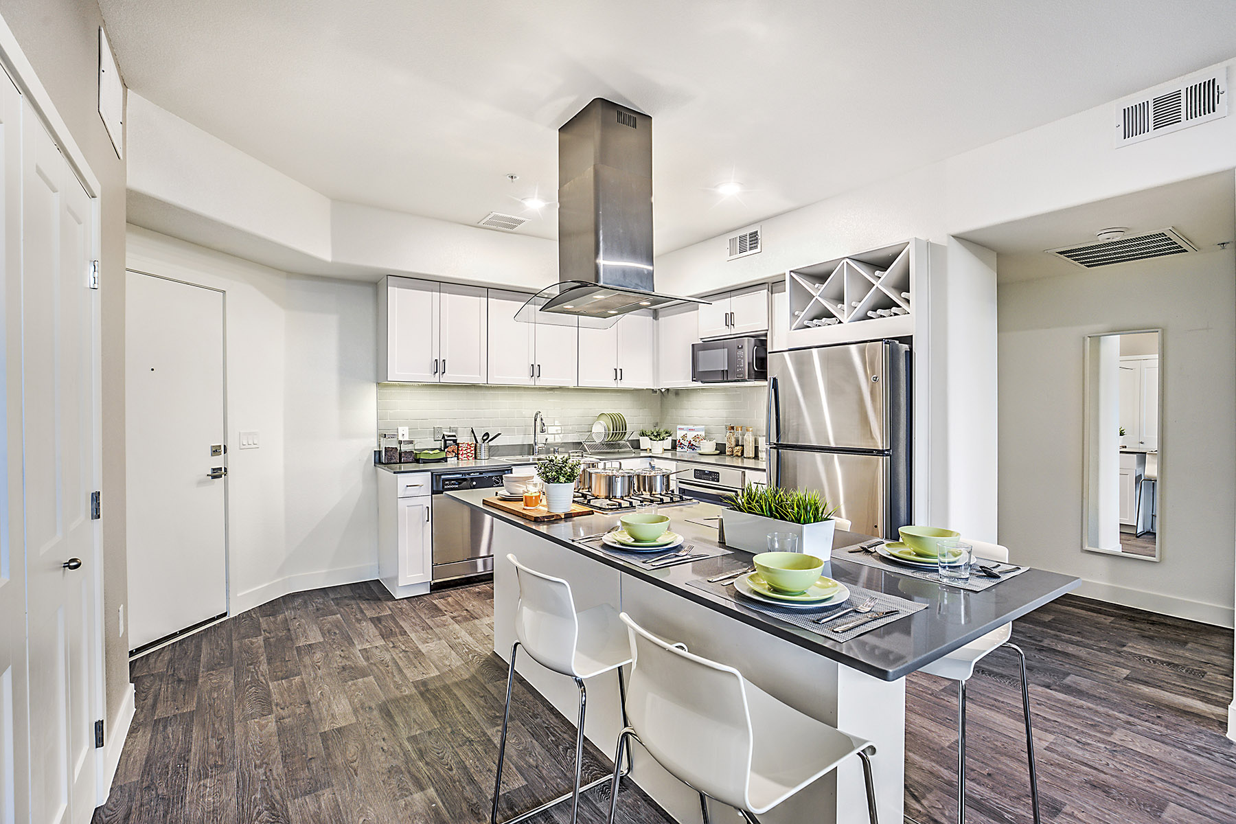 Open-concept kitchen with large island set up with dinner placements, stainless steel appliances, and white cabinetry.