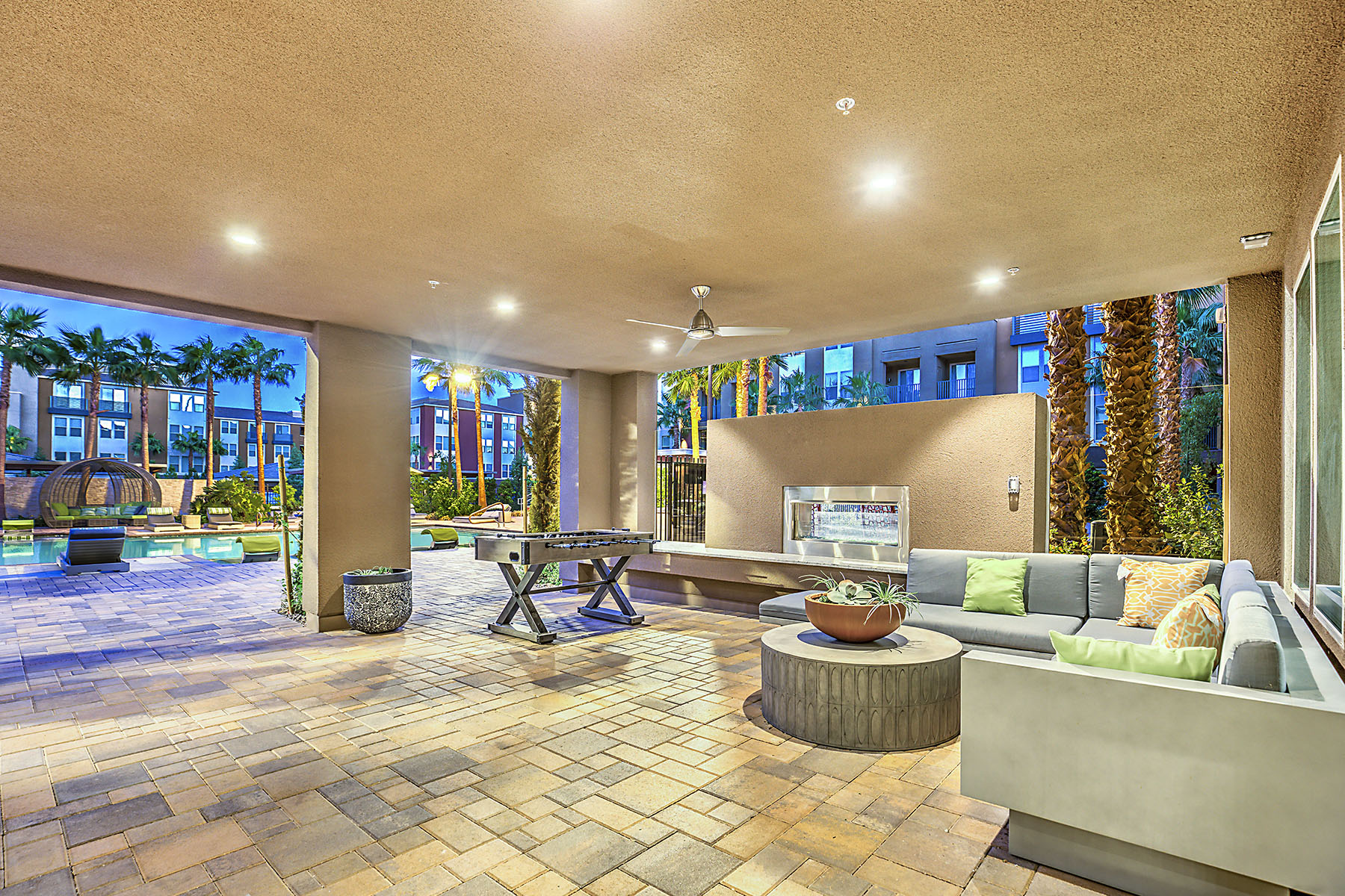 Outdoor lounge and entertainment area with ceiling fan, fireplace, couch, and foosball table. The deck leads into the resort-style pool area.