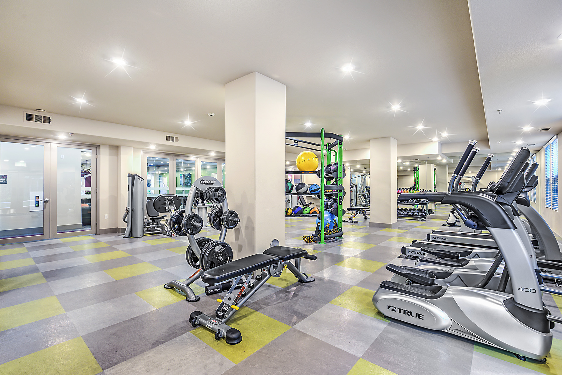 Spacious fitness center with exercise balls, dumbbells and medicine balls, weight machines, and cardio machines including treadmills and ellipticals.