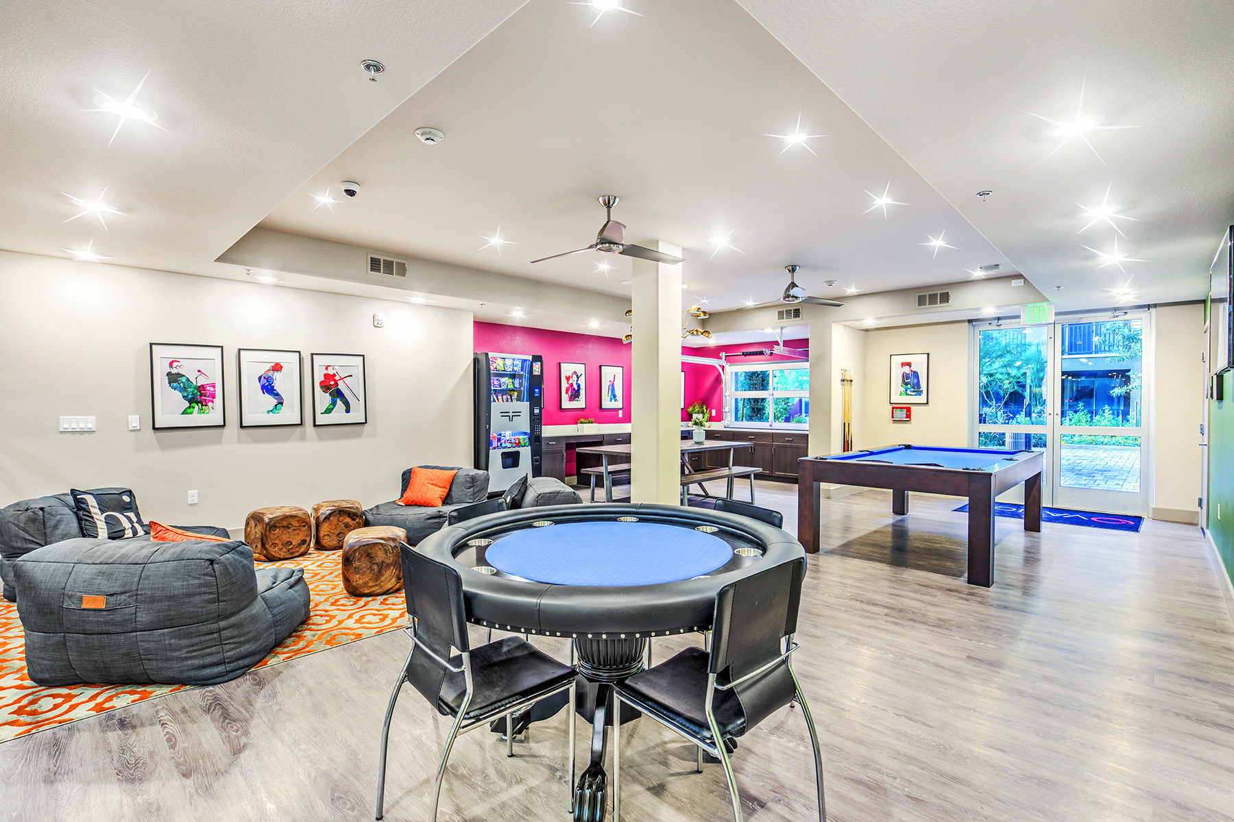 Expansive entertainment and dining room with glass doors leading to the patio. There is vibrant interior design, a poker table, large bean bag and memory foam seating, a pool table, plus a spacious kitchen with dining table and vending machine.