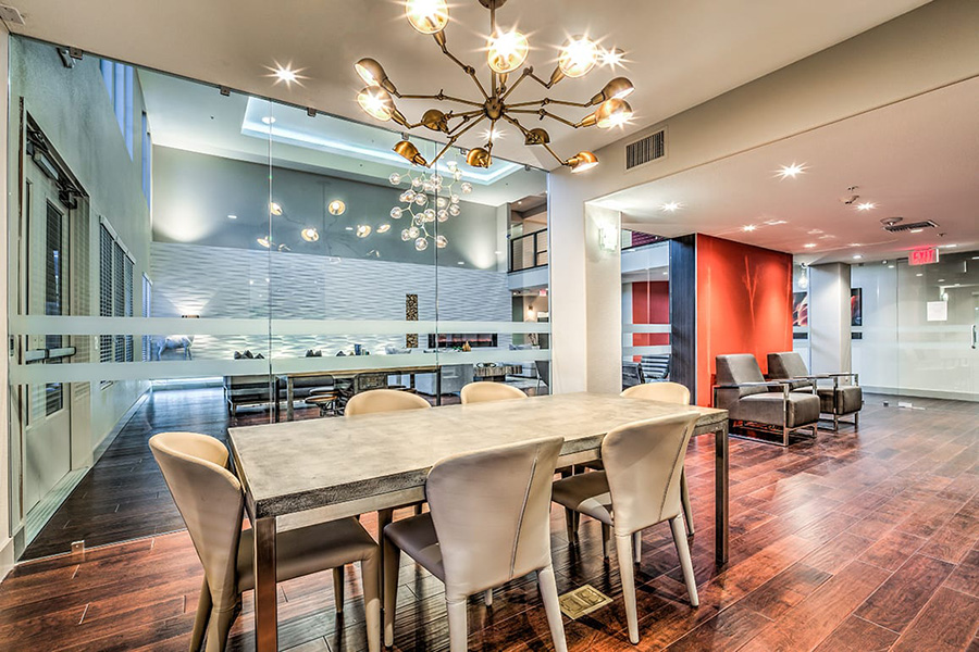 Spacious community clubhouse at Inspire with interior glass walls, sleek furniture, and designer lighting There is a spacious lounge as well as conference room seating.