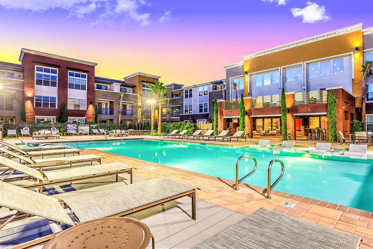 Resort-style pool with in-pool chaises, lounge chairs, plush daybeds, and tables and chairs outside of the community clubhouse and mid-rise apartment buildings.