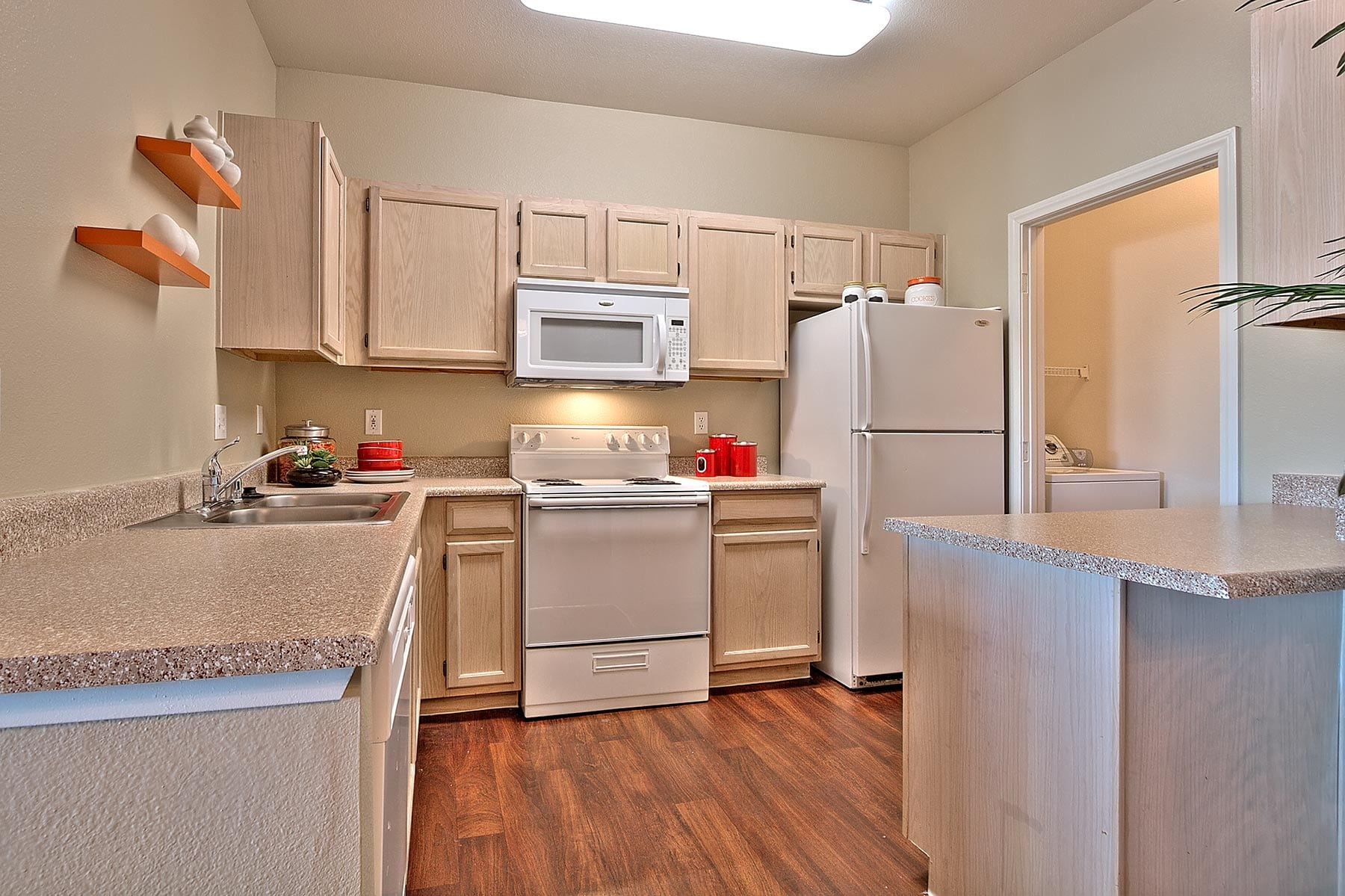 A San Croix apartment kitchen with smooth countertops, rich wood-like flooring, and matching appliances.