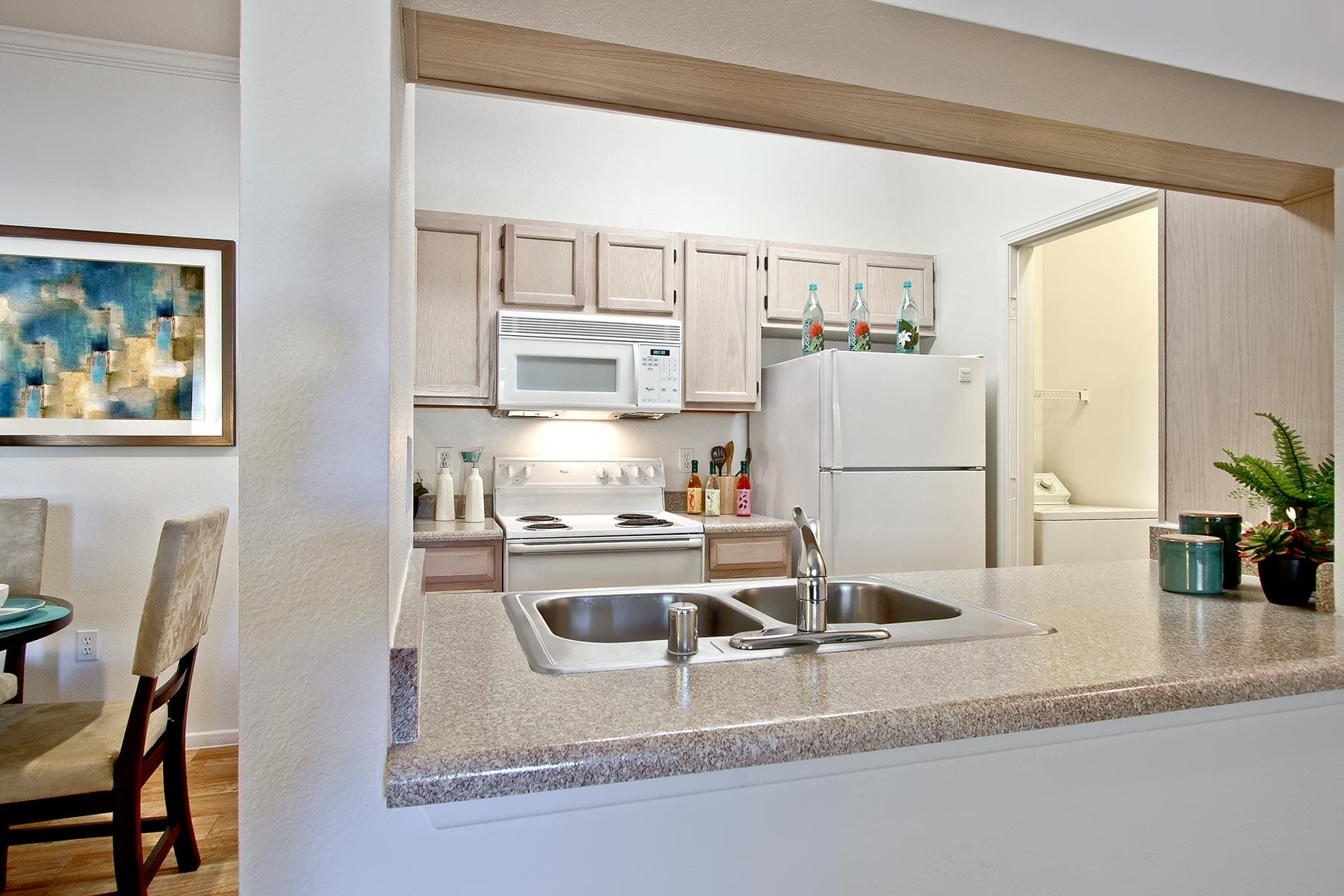 A kitchen with matching appliances, smooth countertops and a stainless steel sink.