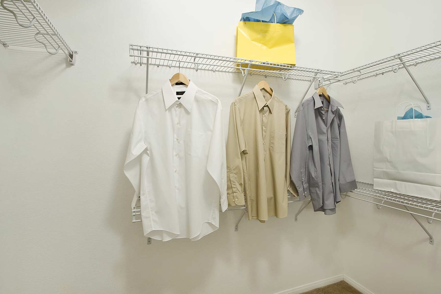 A spacious closet with a selection of shirts and shelves supporting shopping bags.