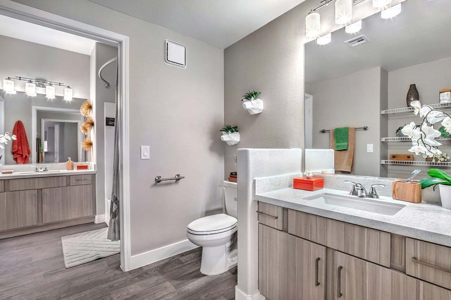 A bathroom with rich wood cabinets, smooth countertops, and planters hung from the wall.
