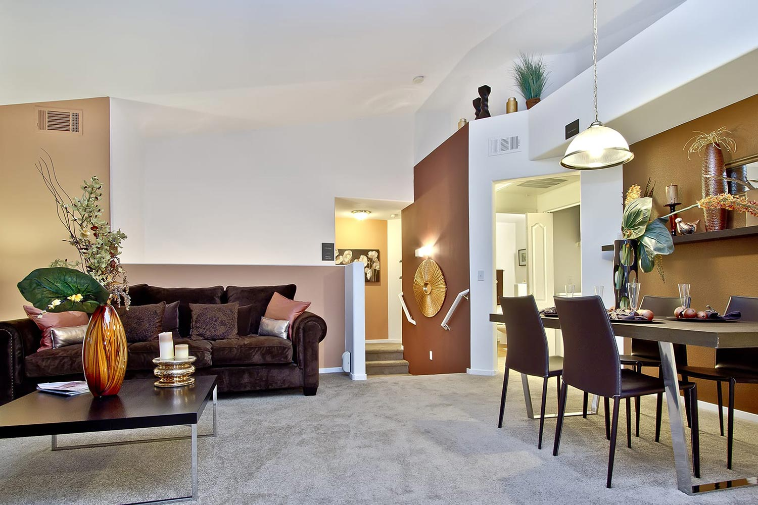 A living and dining room with tall vaulted ceilings, soft carpets, and comfortable furniture.