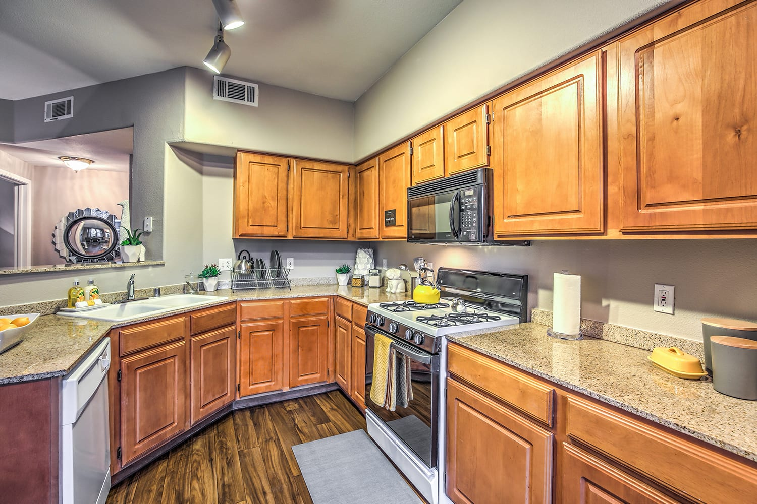 A warm kitchen with wooden cabinets, matching appliances, and smooth countertops.