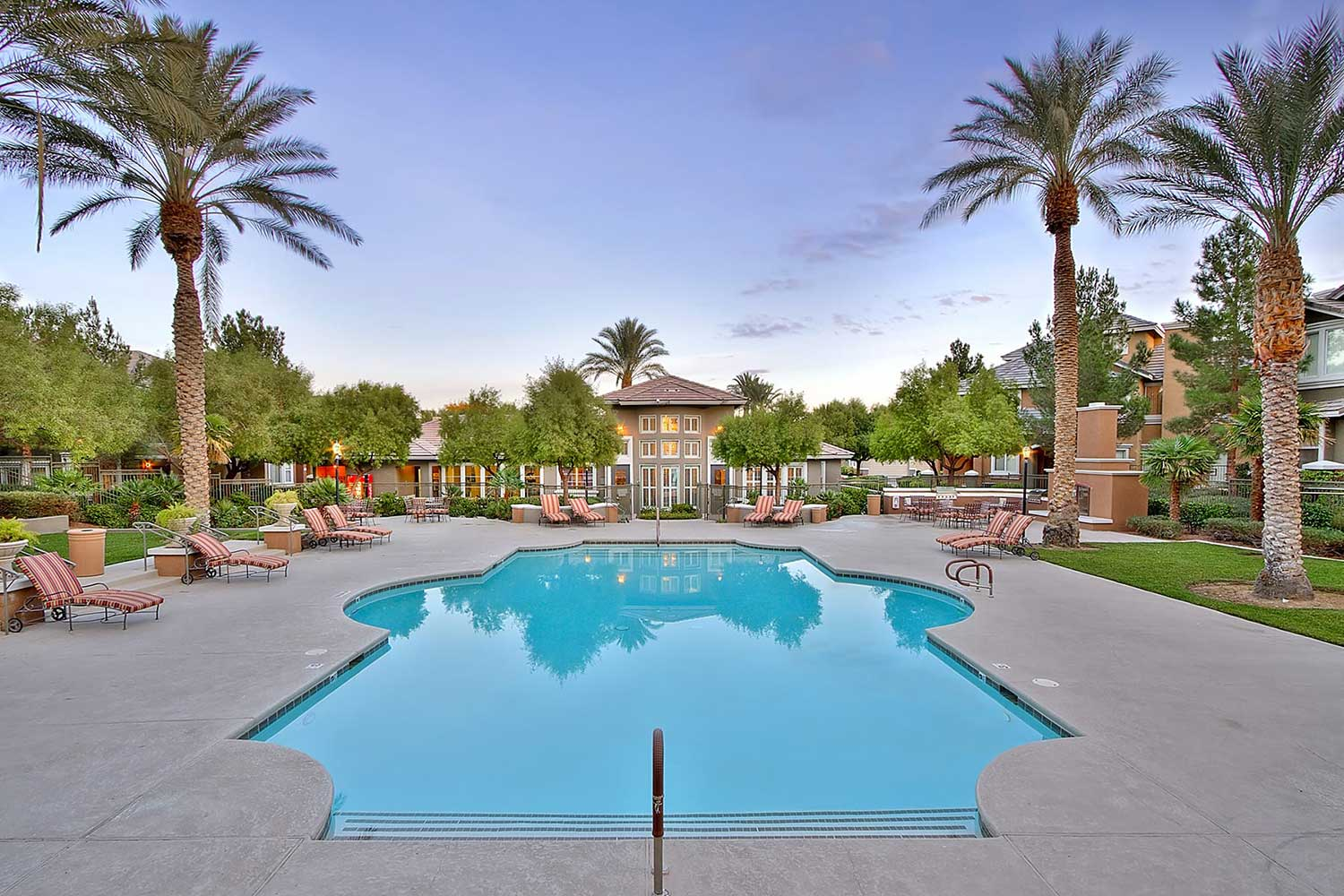 Tuscany's pool courtyard ringed with palm trees and comfortable lounge furniture.