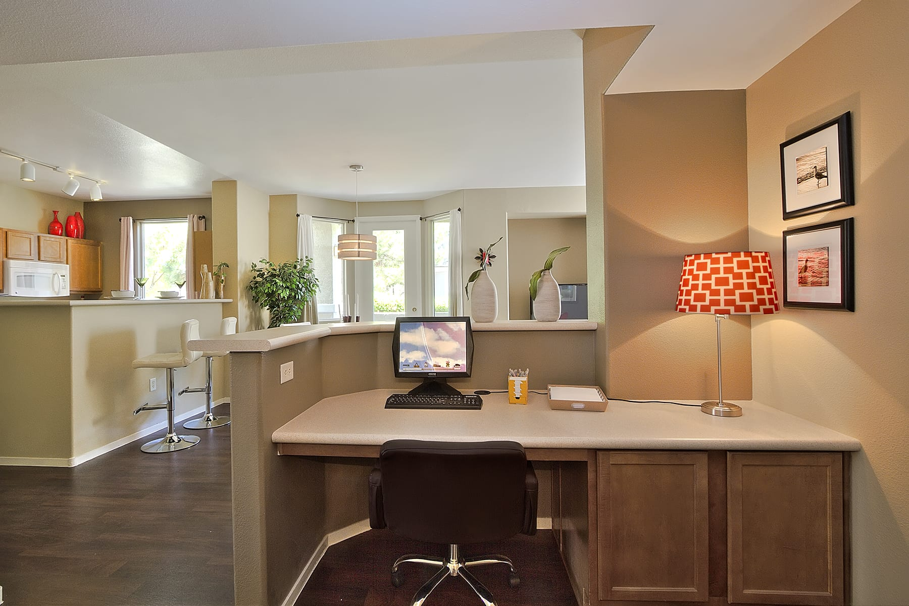 A built-in computer desk overlooks a comfortable living room and kitchen.