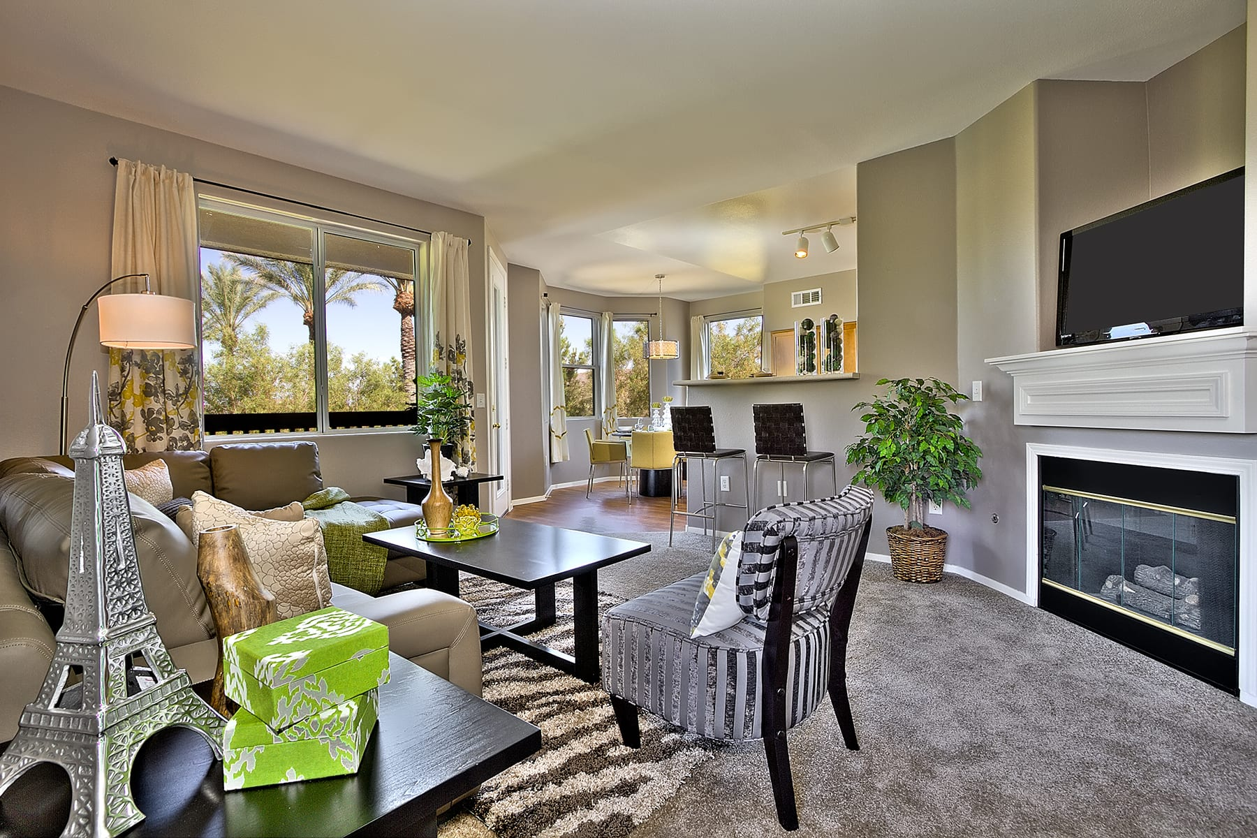 A warm fireplace and plush carpet create a comfortable and inviting space in this furnished living room.