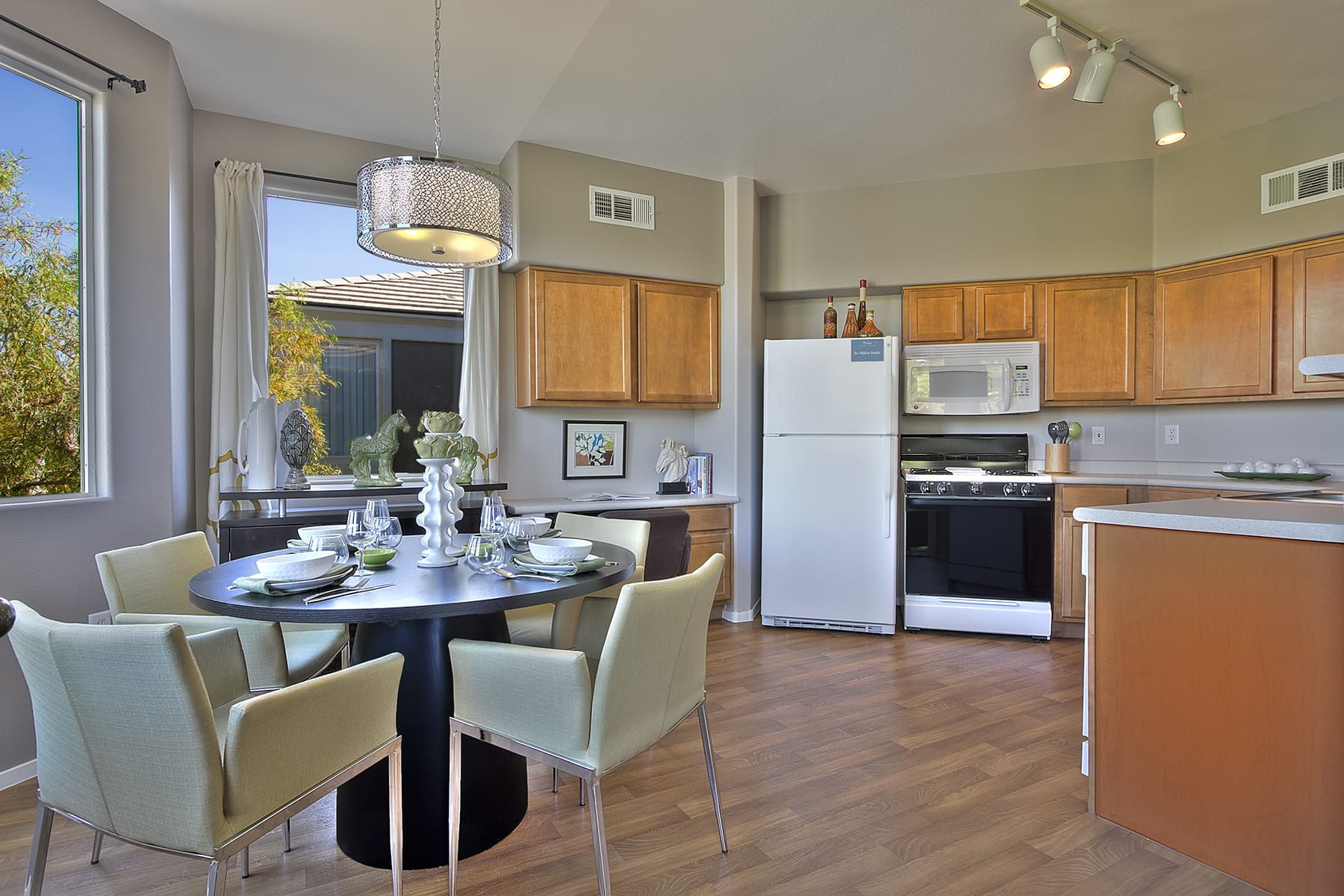 A kitchen with wooden cabinets, matching appliances, and a modern dining table.