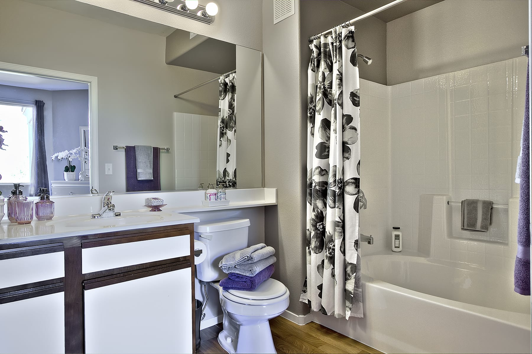 A bathroom with rich wood-like floors and luxurious appointments.