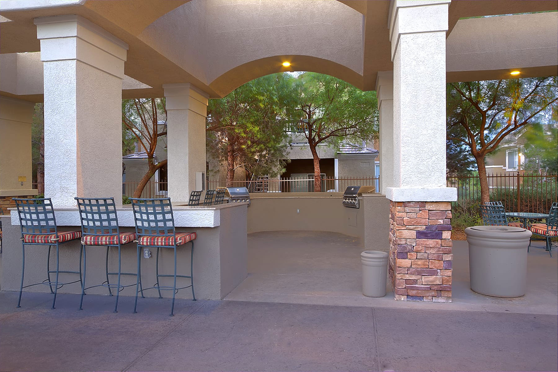 An inviting outdoor covered patio space with a bartop surface, comfortable stools and built in BBQ grills.