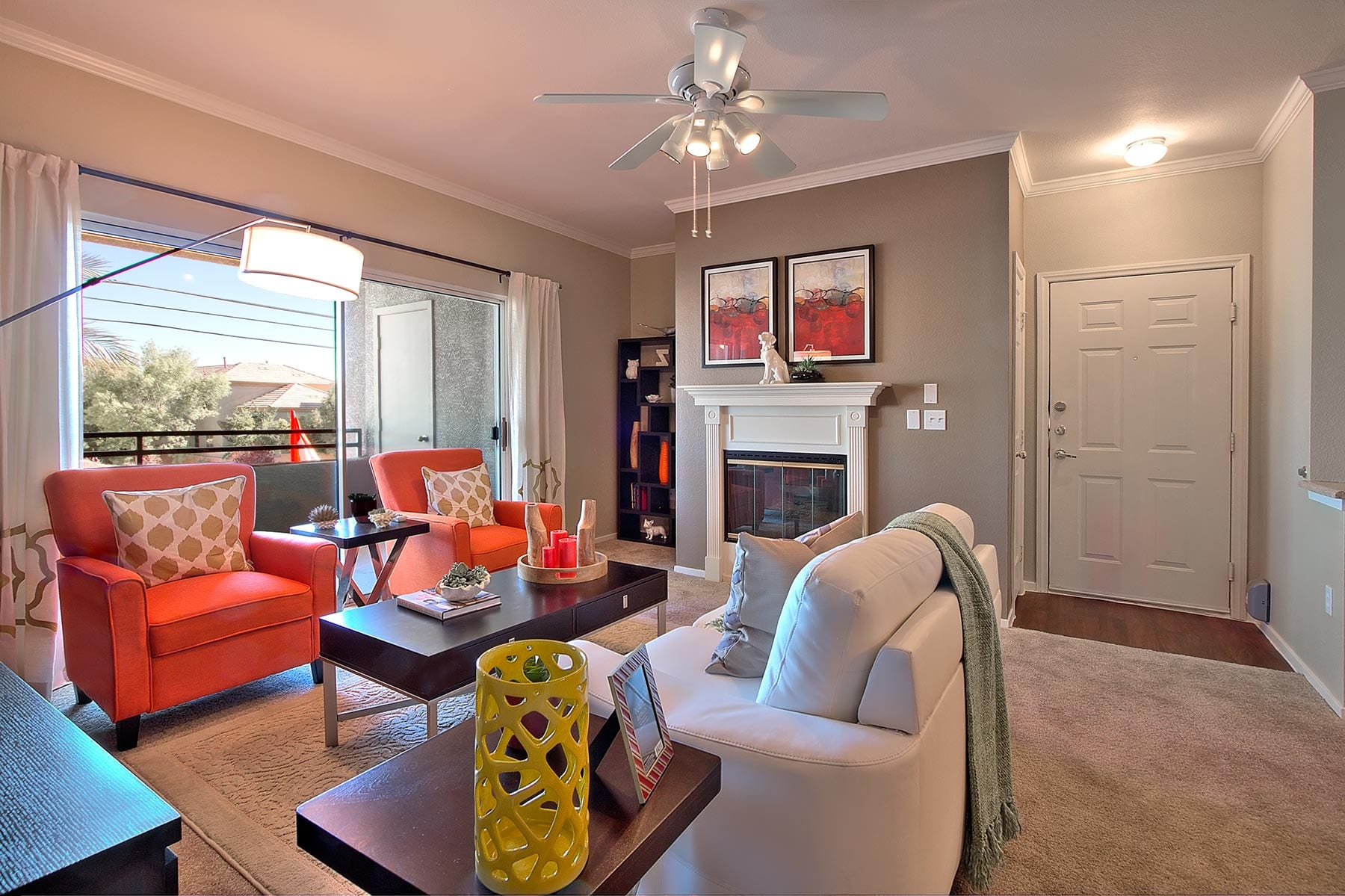 A comfortable living room with plush furniture, soft carpeting, and a bright, wide patio door.