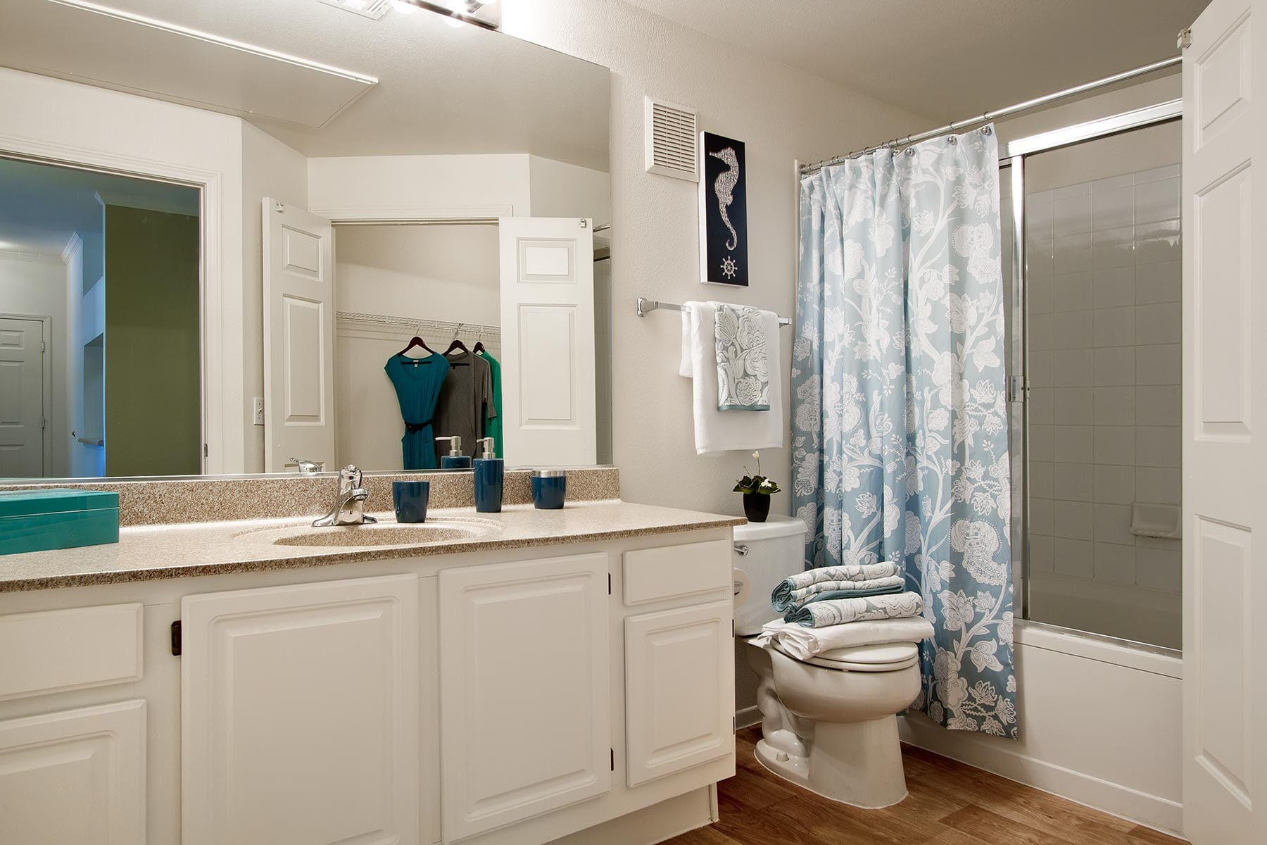 A bathroom with plush plush towels, smooth countertops, and a sliding glass shower door.