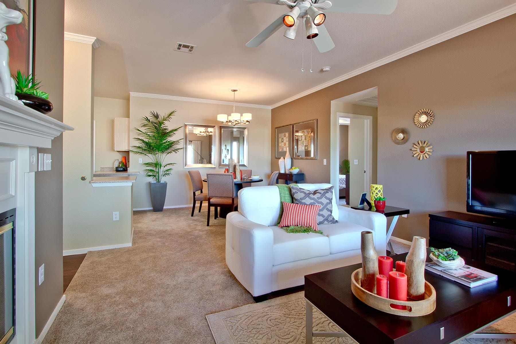An inviting living/dining space with soft carpeting, plush seating, and a warm fireplace.
