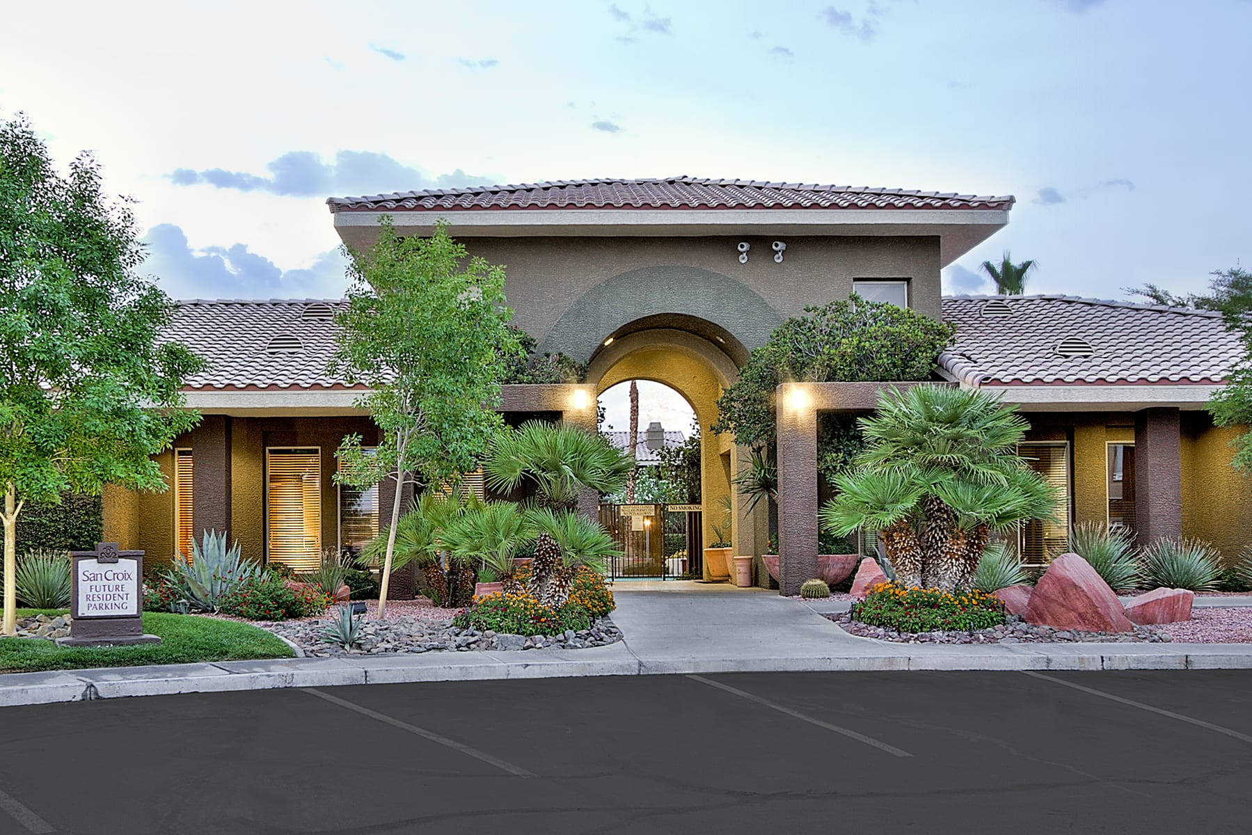 Ample parking and lush landscaping lead towards the tall entrance archways of San Croix Apartments.